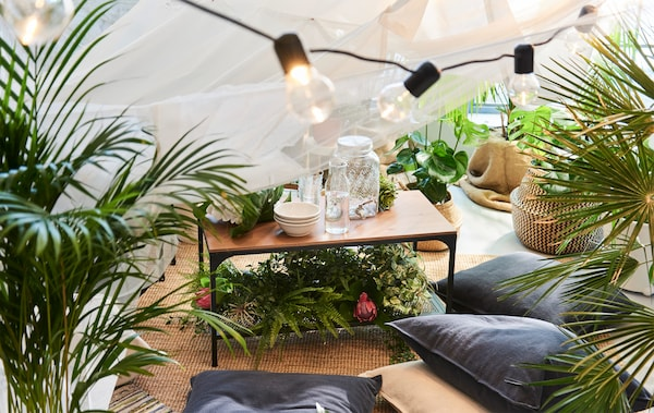An IKEA FJÄLLBO coffee table in black metal and solid wood under a white canopy with string lights
