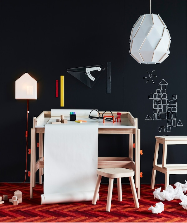 An IKEA FLISAT children's desk in wood with a built in drawing paper roll holder, set before a black wall.