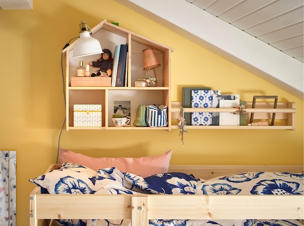 An IKEA FLISAT pine dollhouse mounted on a wall and used to store toys above a bunk bed.