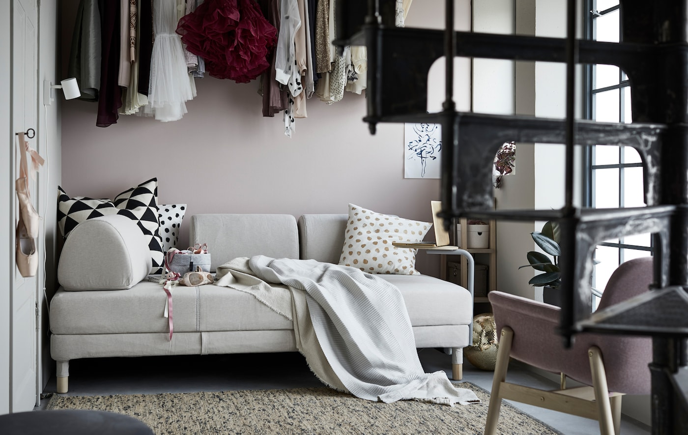 An IKEA FLOTTEBO sleeper sofa in a room that includes a spiral staircase and hanging clothes above the sofa.