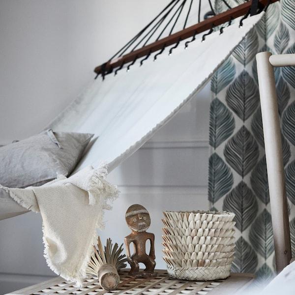 An IKEA FREDÖN hammock in a bedroom, beside an IKEA HOL side table with decorative accessories.