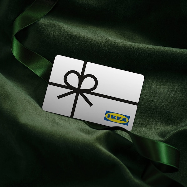 An IKEA gift card relaxing on a beautiful, soft bed of green fabric.