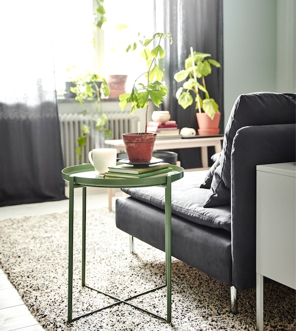 An IKEA GLADOM tray table in dark green with a removable tray top, next to a gray sofa in front of a window.