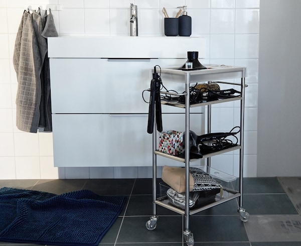 An IKEA GRUNDTAL cart stocked with blowdryers, curling irons, and other accessories stands in front of a bathroom sink.
