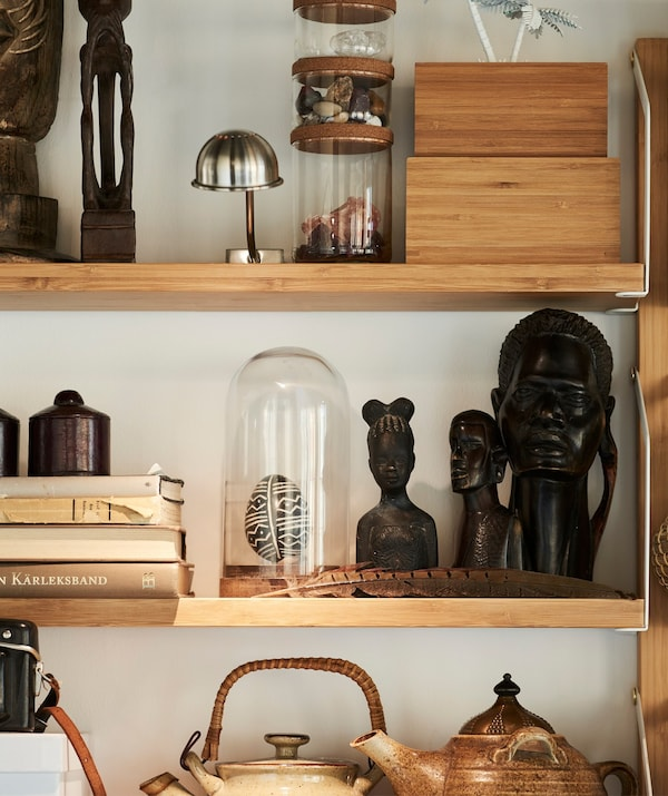 An IKEA HÄRLIGA glass dome on a shelf surrounded by a collection of souvenirs.