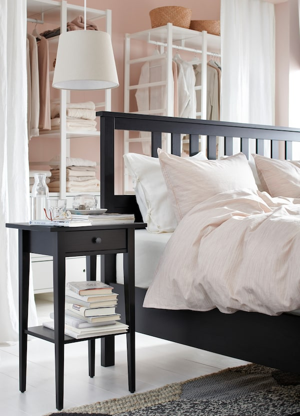 An IKEA HEMNES black brown bed frame with a slatted headboard, bedside table and pink bedding.