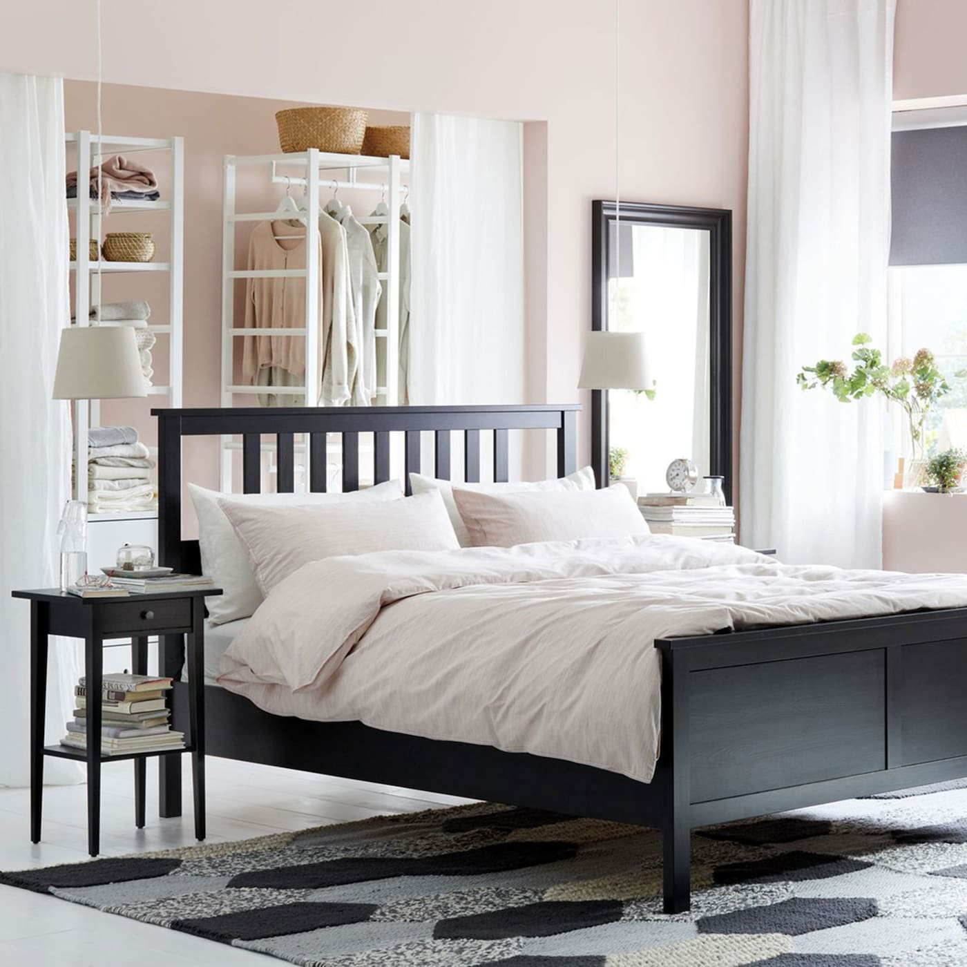 An IKEA HEMNES black brown bed frame, with straight slats on the headboard, positioned bodly in the middle of a pink bedroom.