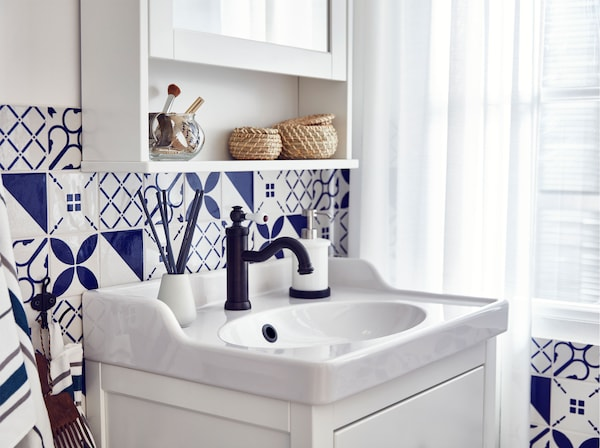 An IKEA HEMNES/RÄTTVIKEN white wash-stand with smooth-running and soft-closing drawers, in a blue and white tile bathroom.