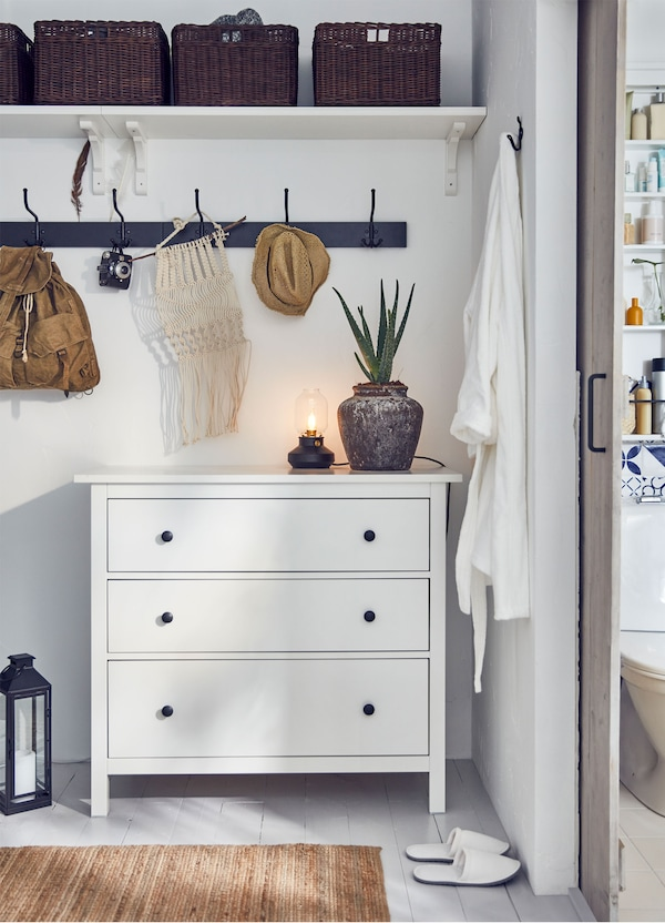 An IKEA HEMNES white chest of 3 drawers in a bedroom, with a rail and shelf above holding baskets.