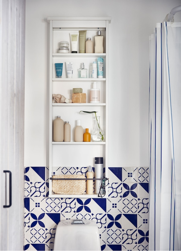 An IKEA HEMNES white wall shelf unit, holding bathroom accessories, above a toilet in a blue and white tiled bathroom.