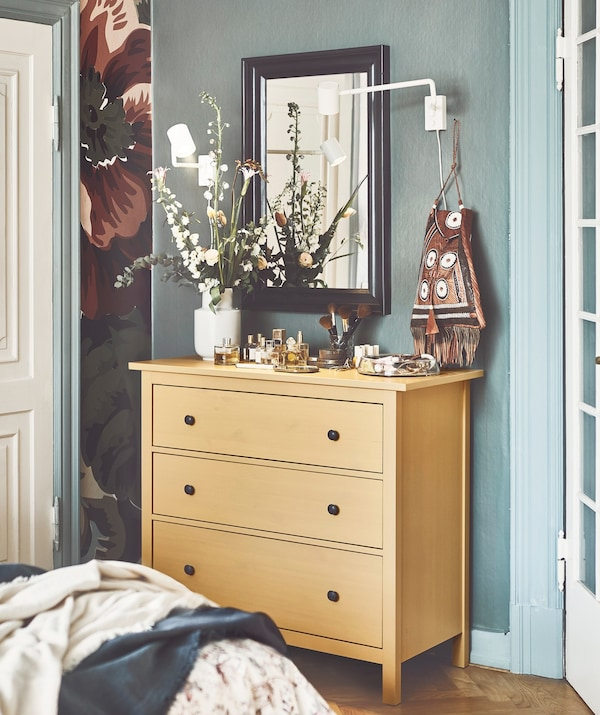 An IKEA HEMNES yellow chest of 3 drawers in a bedroom.