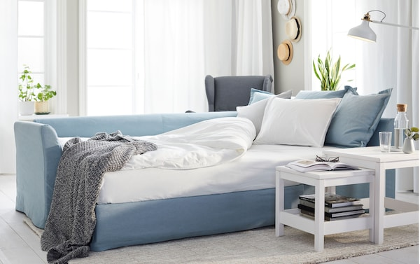 An IKEA HOLMSUND sofa-bed set up as a bed with pillows and covers, near a nest of HAVSTA white tables.