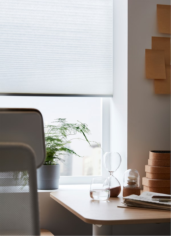 An IKEA HOPPVALS cellular blind, with a honeycomb structure, at a window, behind a work desk and chair.
