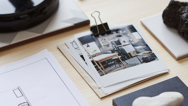 An IKEA interior design photograph in a pile held by a bulldog clip, next to the corner of a sketch plan, on a wooden table.