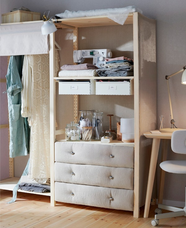 An IKEA IVAR 3-drawer chest with fabric fronts to the drawers. Sewing accessories in vases decorate the top.