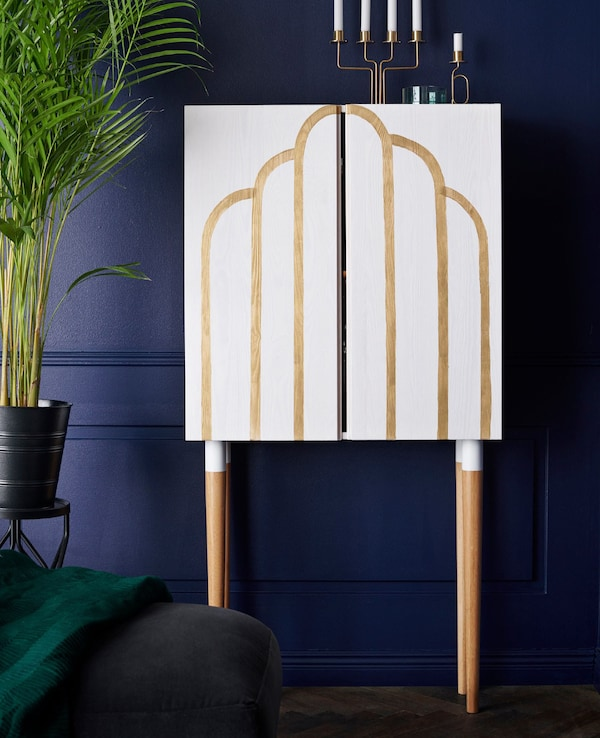 An IKEA IVAR cabinet in solid wood that has been painted with a motif, placed against a blue wall.