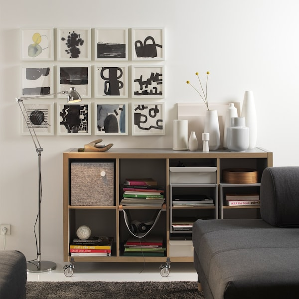 An IKEA KALLAX grey/wood shelving unit with lots of vases on top and lots of artwork on the wall.