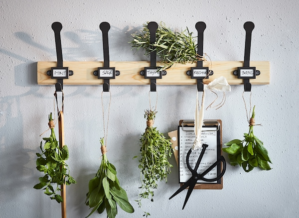 An IKEA KARTOTEK pine rack pimped as an herb rack, with five black hooks used to hang herbs and scissors.