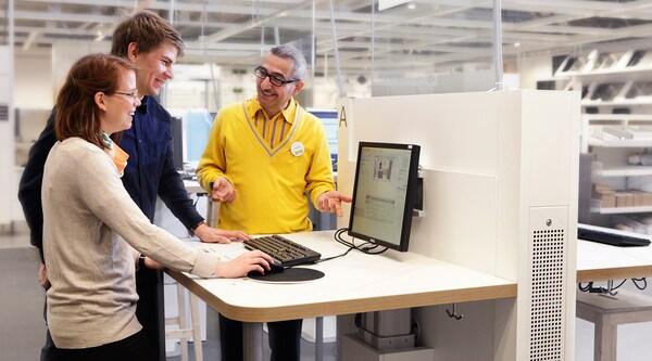 An IKEA kitchen expert assisitng a couple