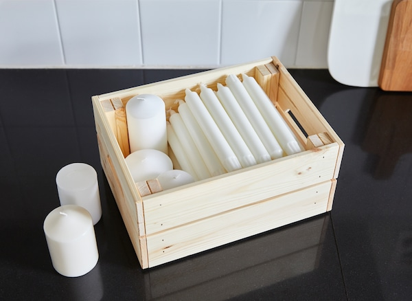 An IKEA KNAGGLIG pine box used to store white candles.