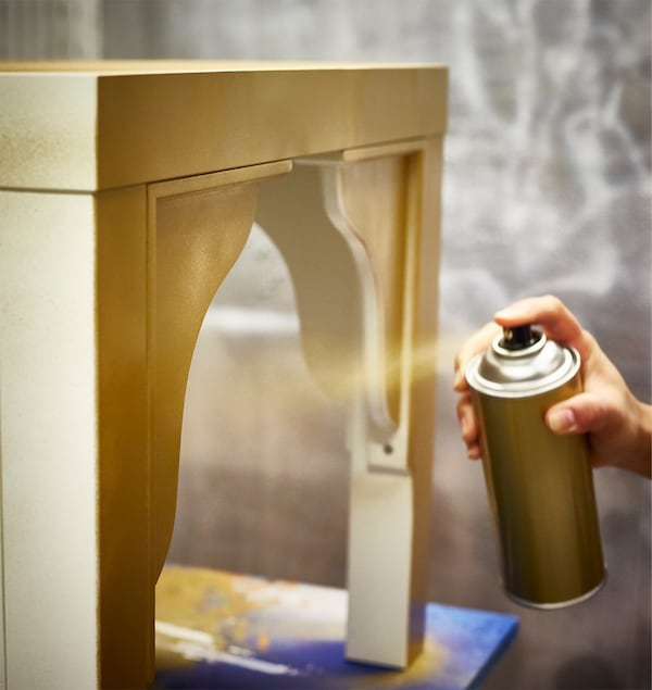 An IKEA LACK table is being spray-painted gold.