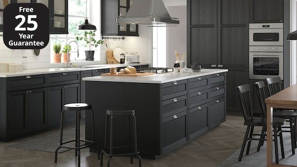 An IKEA LERHYTTAN black stained kitchen with white worktop and traditional, metal handles.