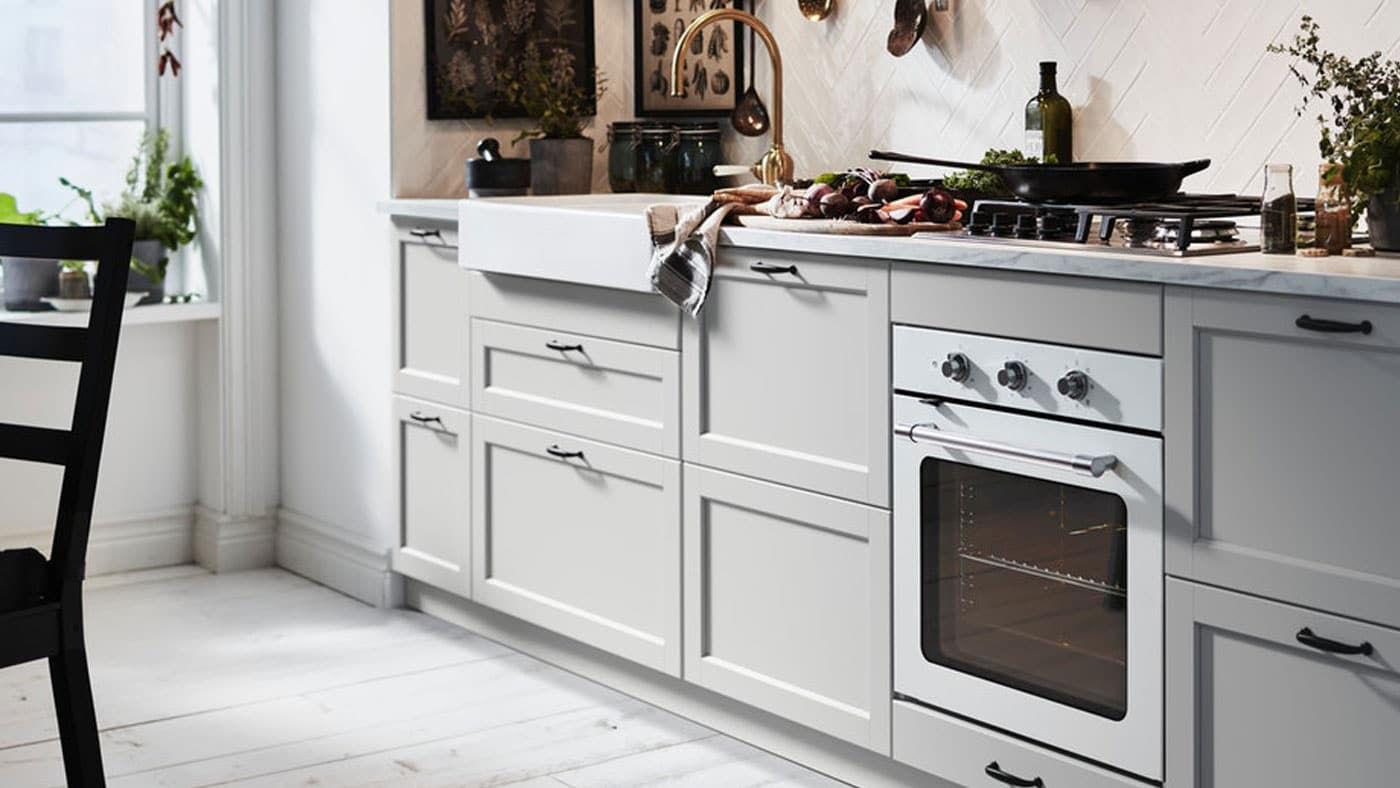 An IKEA LERHYTTAN light grey kitchen with white worktop and black, slimline handles.