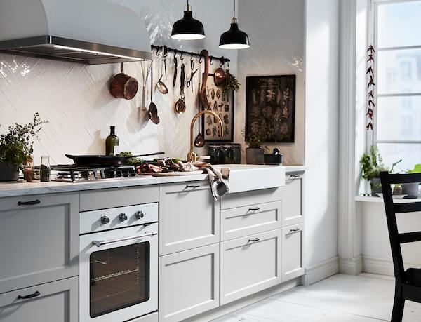 An IKEA LERHYTTAN light grey kitchen with white worktop and black, slimline handles.