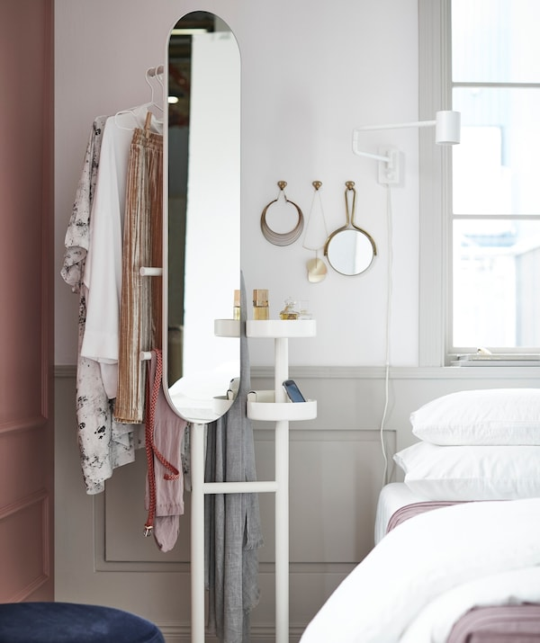 An IKEA LIERSKOGEN valet stand with mirror, next to a bed.