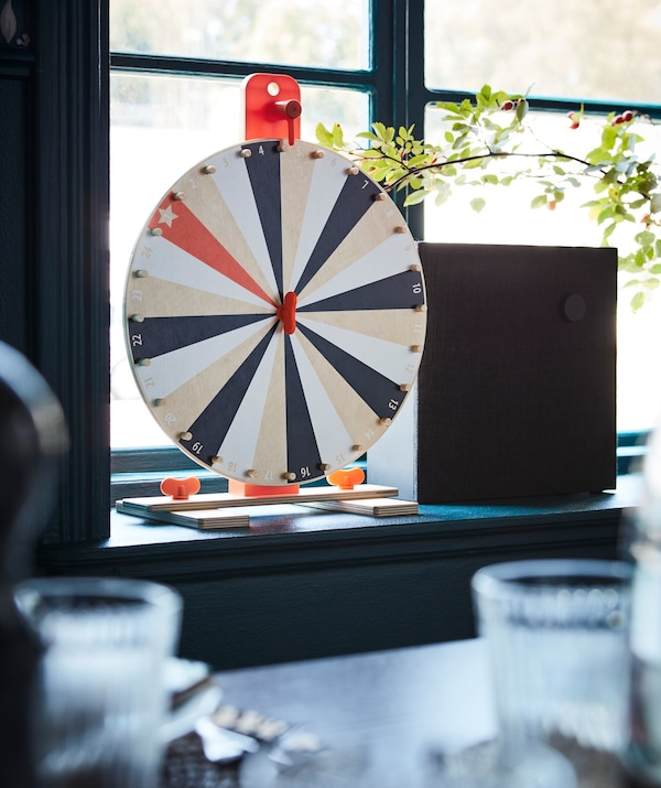 An IKEA LUSTIGT wheel of fortune game placed on a window sill.