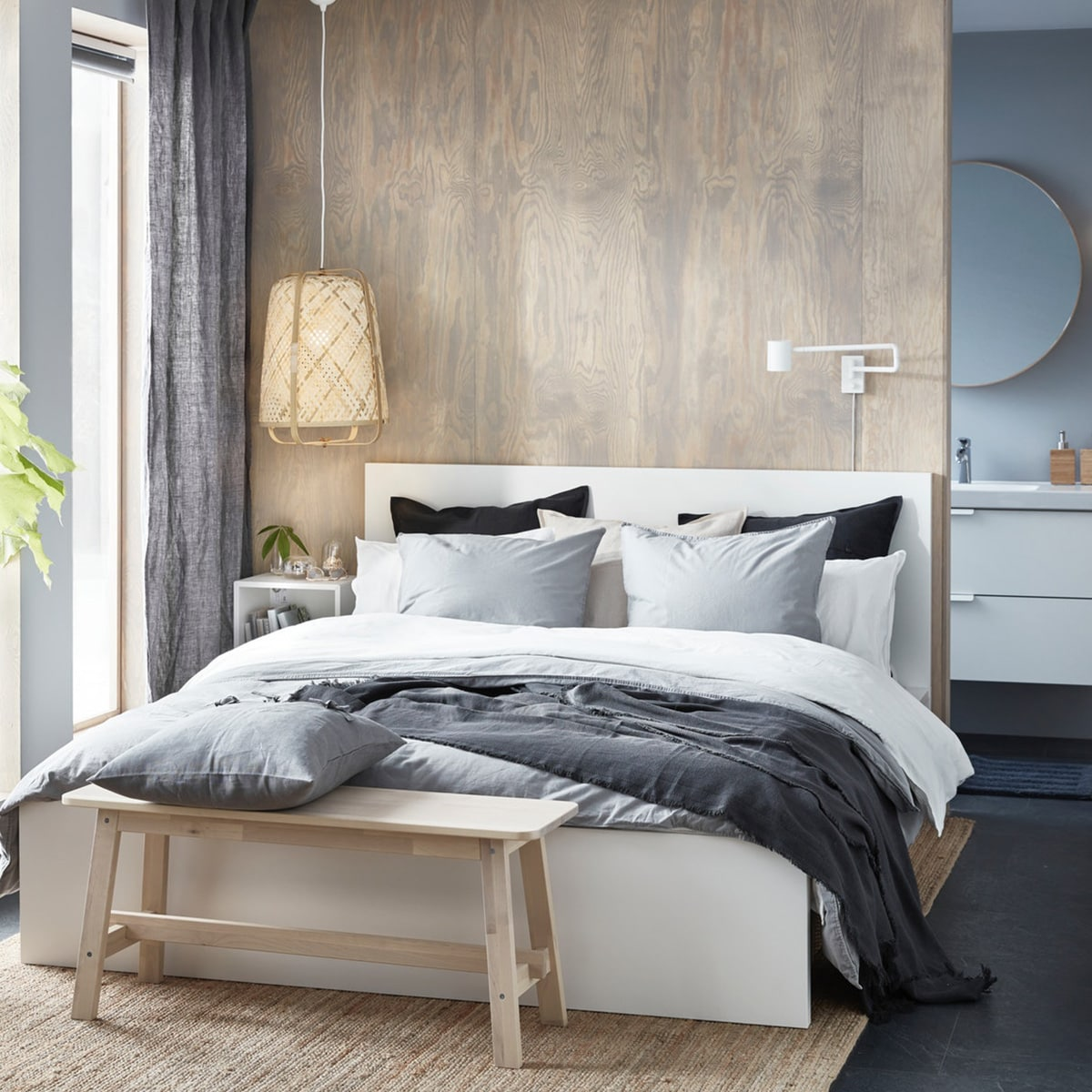 An IKEA MALM high white bed frame, with white and grey bedding in a small bedroom with wood accents.