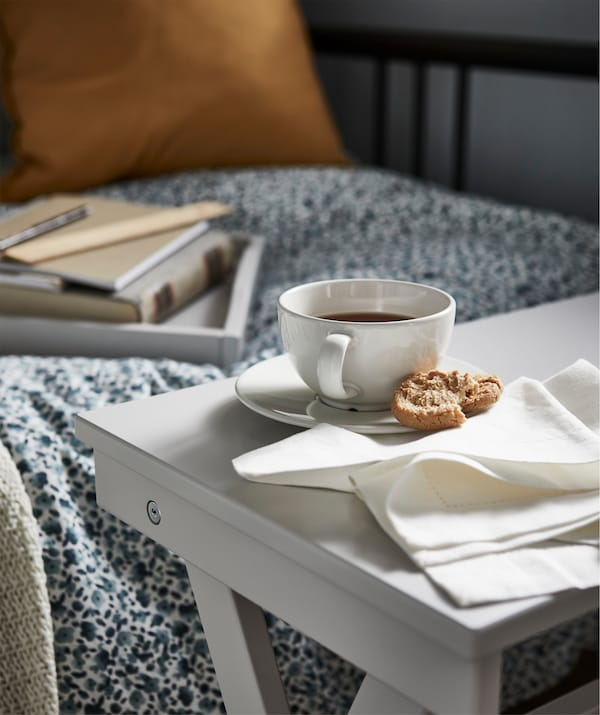 An IKEA MARYD tray table holding a coffee cup and napkins near a day bed.