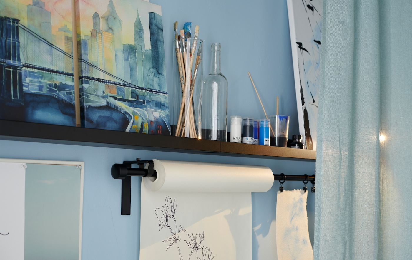 An IKEA MOSSLANDA black picture ledge with brushes, jars and art on show.