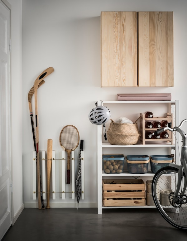 An IKEA MOSSLANDA hack stores sports equipment vertically in a garage with other storage solutions, like a cabinet.