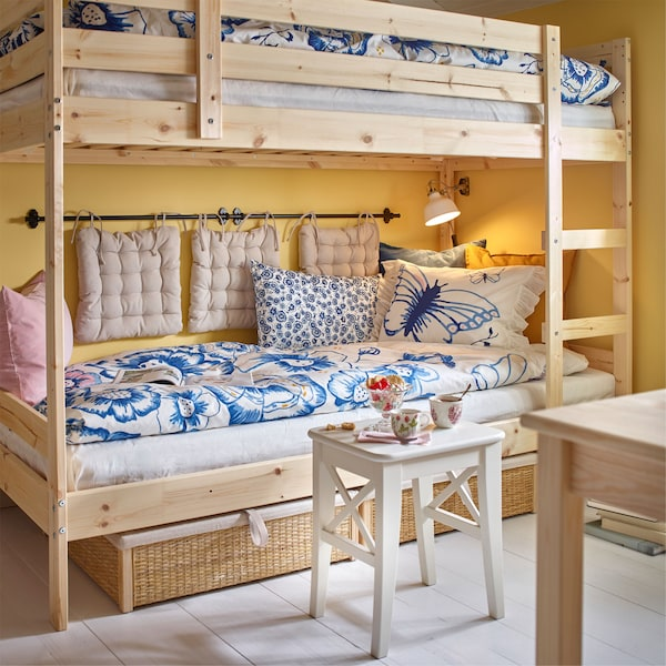 An IKEA MYDAL bunk bed, with the lower bunk used as a daybed, with extra cushions hung on the wall and blue floral bed linen.