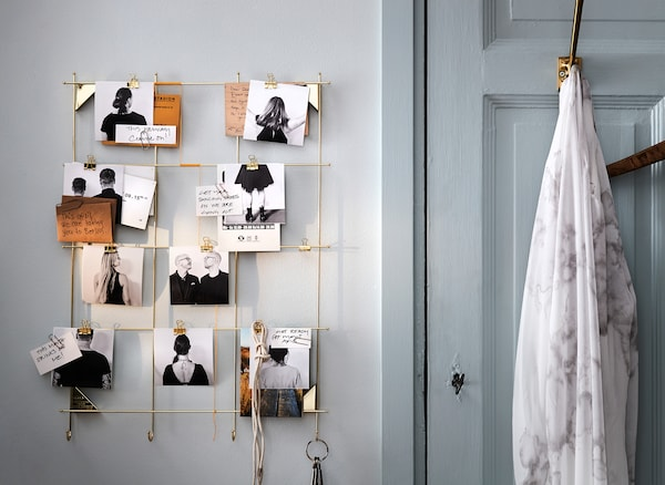 An IKEA MYRHEDEN brass wire frame used as a DIY wall activity calendar, with photos and notes clipped to the frame.