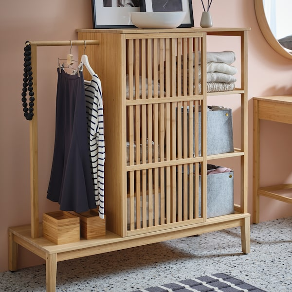 An IKEA NORDKISA open wardrobe that is made from bamboo is filled with storage baskets, clothing and accessories.
