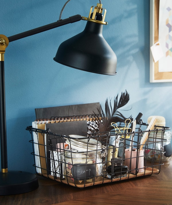 An IKEA PLEJA wire basket shown on a desk and full with ornaments, notebooks and desk accessories.