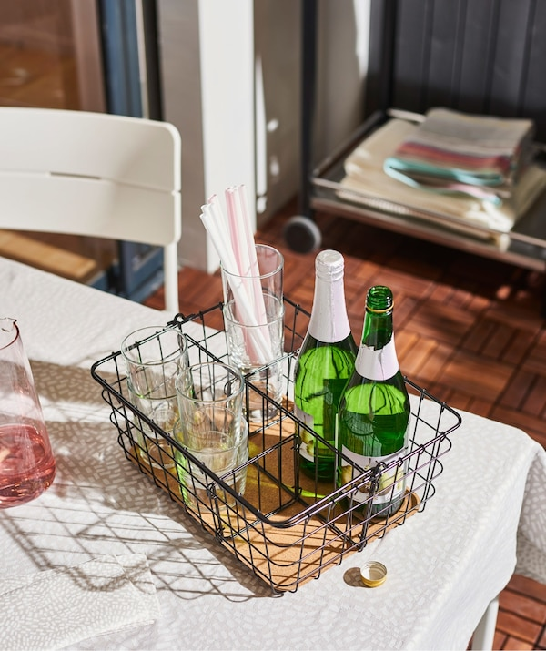 An IKEA PLEJA wire basket with handle in black steel and cork, set on a table and filled with bottles.