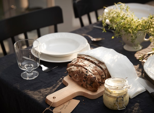 An IKEA PROPPMÄTT beech chopping board doubles as a rustic serving tray on a dining table set for lunch.