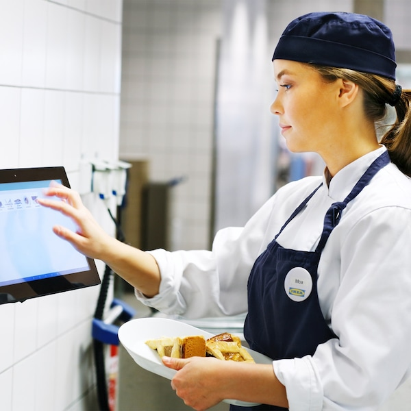 An IKEA Restaurant co-worker identifying food waste on a tablet while holding a plate of food.