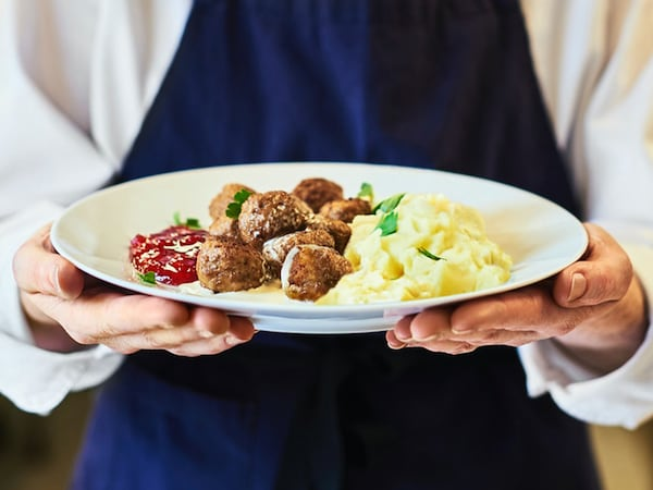 An IKEA Restaurant co-worker wearing a blue apron holding up a plate of meatballs with mashed potato, cream sauce and ligonberry jam.