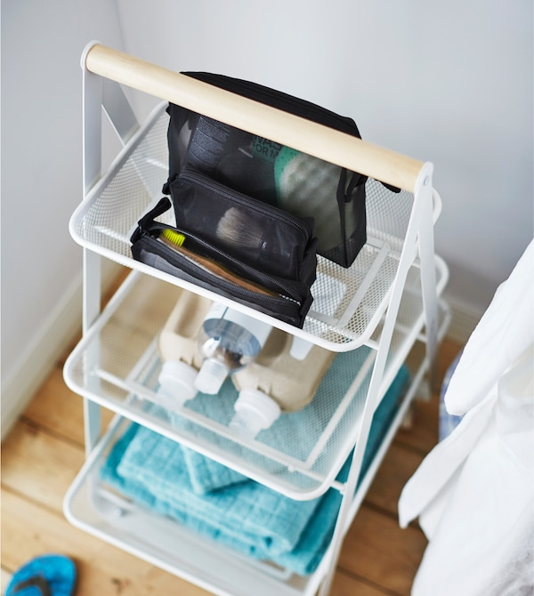 An IKEA RISATORP trolley holds bathroom essentials like towels, shampoo and soap.