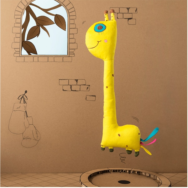 An IKEA SAGOSKATT soft toy – a happy, yellow giraffe jumping in the air in front of a cardboard castle.