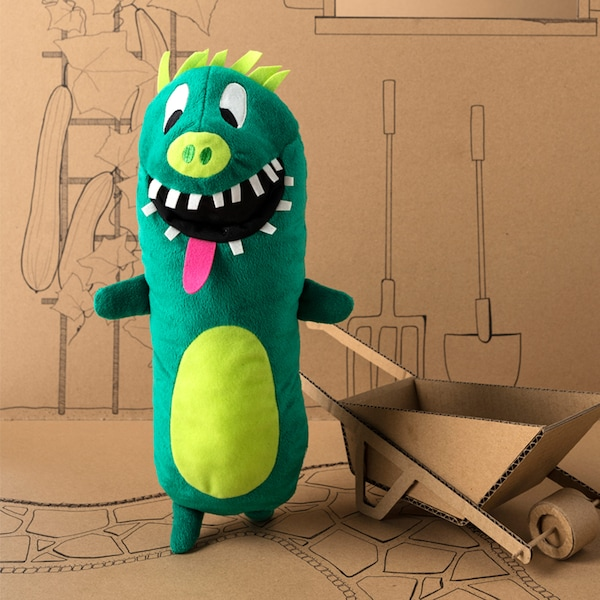 An IKEA SAGOSKATT soft toy that's a green cucumber superhero with hair, teeth and a pink tongue.