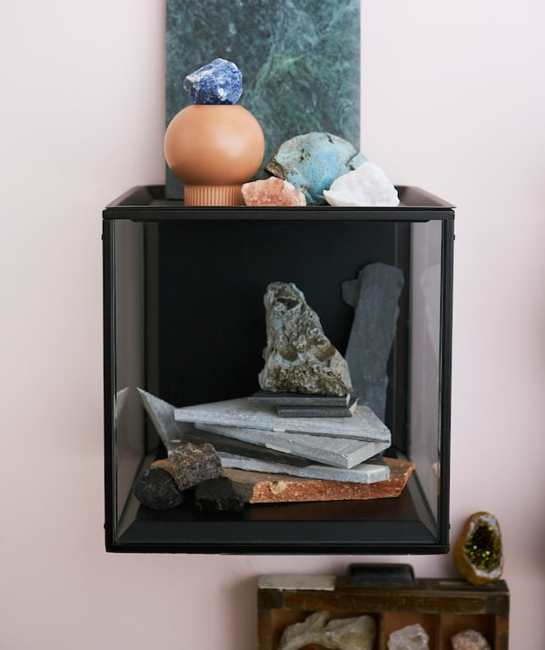 An IKEA SAMMANHANG display box filled with stones and crystals.