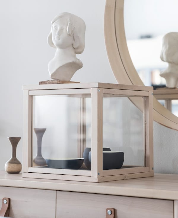 An IKEA SAMMANHANG display case on a cabinet, filled with a collection of bowls.