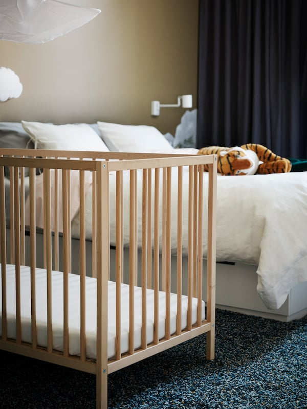 An IKEA SNIGLAR wooden crib in a carpeted bedroom with a double bed and a tiger soft toy and blackout curtains.