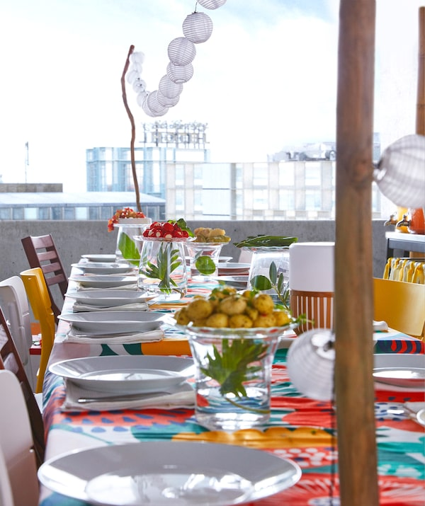 An IKEA SOLARVET LED lighting chain with twelve solar-powered lights hanging over a colourful summer party table.