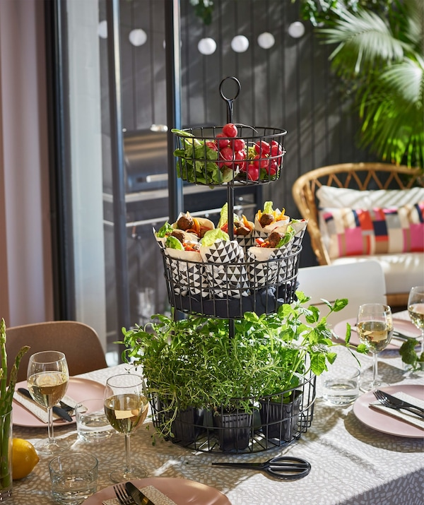 An IKEA SOMMAR 2018 3-tier serving basket in black steel on a dining table, filled with herbs and vegetables.